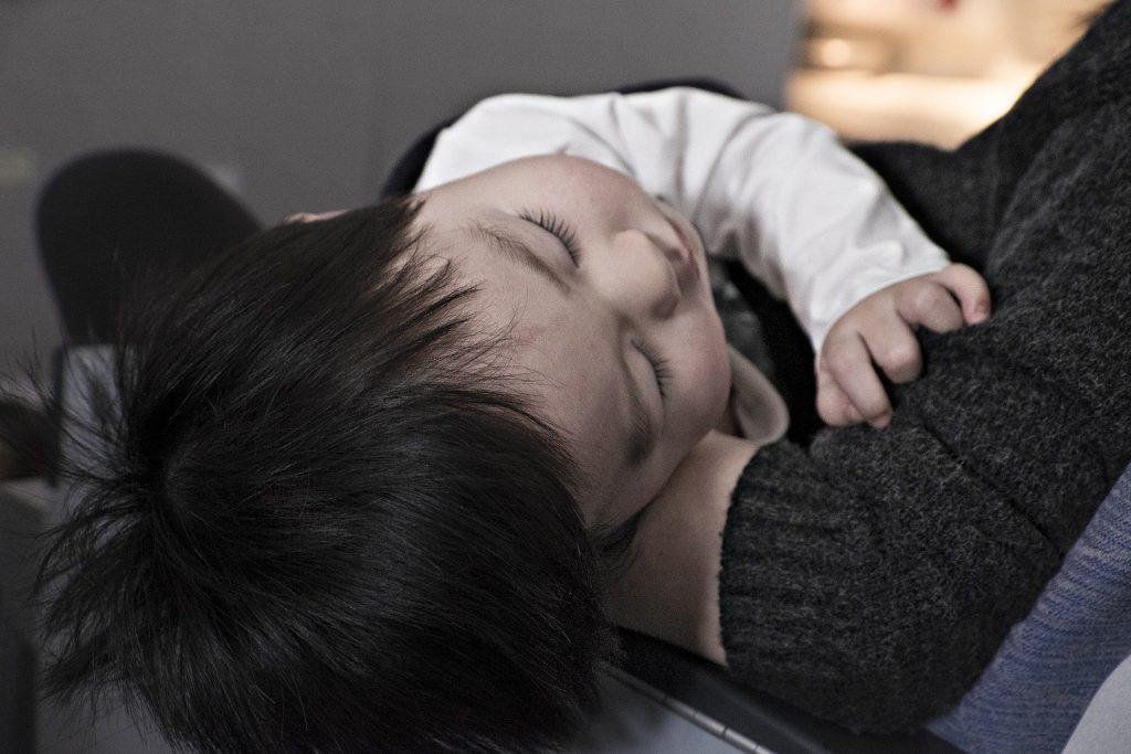 enfant endormi dans les bras de sa mère après un cauchemar