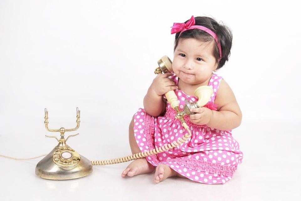 bébé tenant un téléphone pour appeler une consultante en sommeil